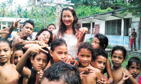 万金玉在太平洋的一个小岛上与孩子们快乐合影。