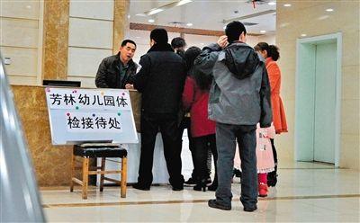 3月16日,在吉林市中心医院内,芳林幼儿园的孩子家长们在体检接待处前登记。经调查,初步认定该幼儿园涉嫌擅自给幼儿服用病毒灵。新华社记者 张楠 摄