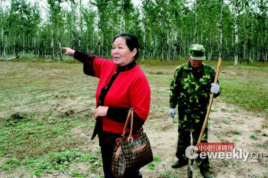 刘玉英,身后是她雇来看护林地的工人 《中国经济周刊》记者 肖翊|摄