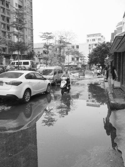 海口一百余米马路污水横流 居民踩砖头通过