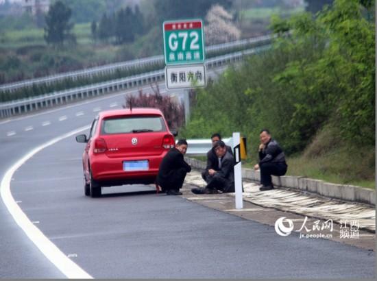 男子将轿车停在高速公路应急车道,三人斗地主,一人围观。