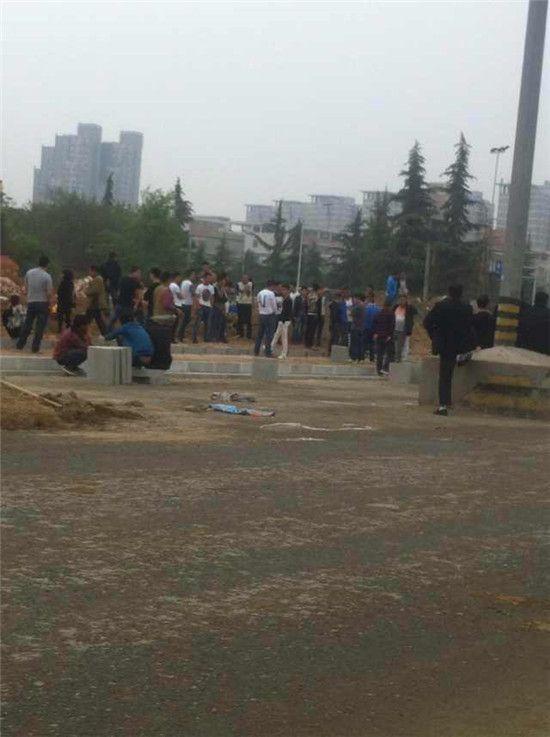 一群不明身份的男子聚集在工地里阻扰施工,而当民工受伤时,这些人悠然地坐在台阶上把玩手机。目击者供图