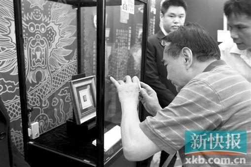 """游客拿出手机拍摄价值500万元的""""红印花小壹圆""""邮票。 新快报记者 祝贺 摄"""
