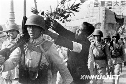 工人在向入城的解放军战士献花(资料照片).-中共为迅速接管南京