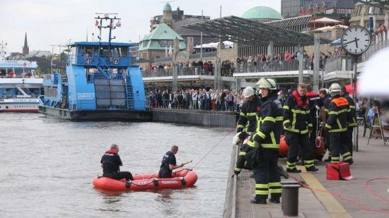 消防队和水上警察正在进行紧张的搜救工作 不远处有数百名围观民众