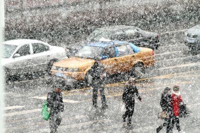 哈尔滨罕见5月飞雪 行人撑起雨伞穿起羽绒服