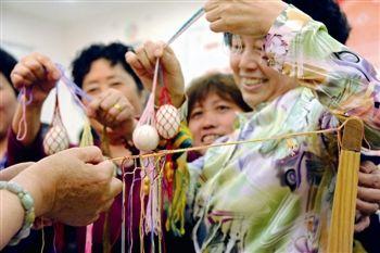 泰州海陵居民编蛋网缝香囊 庆祝端午节