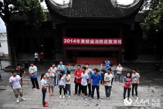2014年5月23日,湖北省宜昌市夷陵區黃陵廟文物管理處消防疏散演練活動中,一名工作人員為游客講解注意事項。