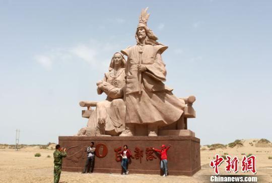 图为游客正在巨人之家雕塑下拍照留念。 李江帆 摄   地处塔克拉玛干沙漠前沿的新疆生产建设兵团第一师十四团昆岗巨人部落的标志性建筑巨人之家雕塑终于揭下神秘面纱,于6月3日正式向游客开放。5日,记者在雕塑下看到,有不少游客正在拍照、留念,一睹古羌人的风采。   据了解,巨人之家雕塑是修建在塔克拉玛干沙漠风积沙地貌之上,面朝塔克拉玛干沙漠腹地,背靠新疆生产建设兵团第一师十四团,其形象定位为曾经生活在塔里木河流域的古羌人。   近年来,随着新疆生产建设兵团第一师范围内考古工作的深入,陆续在该