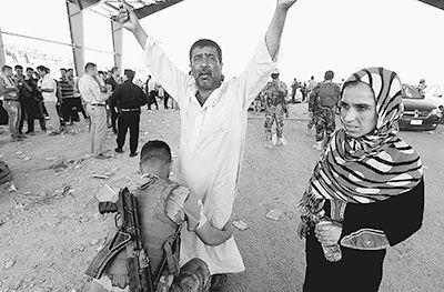 6月10日,在伊拉克库尔德自治区的艾斯基凯莱克检查站,一名安全人员对一名逃离尼尼微省的男子搜身。新华社发