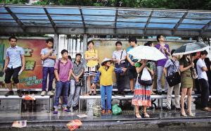 """海口:市民""""登高""""避雨 候车凳很受伤"""