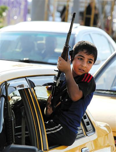 原文配图:16日,巴格达,在一次志愿者集会上,一名男孩拿着枪。面对主要由逊尼派组成的叛军的迅猛攻势,伊拉克什叶派领袖呼吁民众协助政府军作战。伊南部济加尔省省长纳西里说,该省已征召7万名志愿者并设立训练营,大约5000名志愿者已经开赴北部作战。