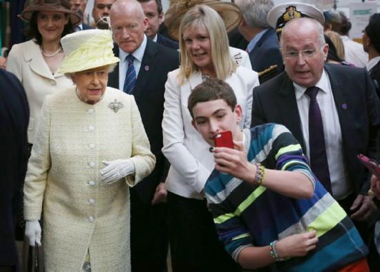 组图:英国女王出访闹市 大胆小伙欲与其自拍
