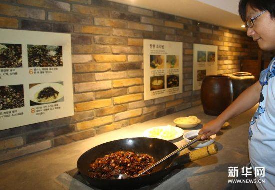 6月28日,在韩国仁川,游客体验炸酱面的制作工序。