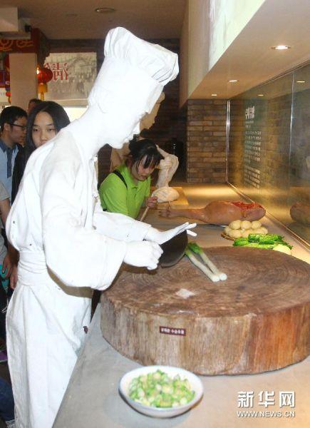 6月28日,在韩国仁川,游客观看炸酱面的制作方法。