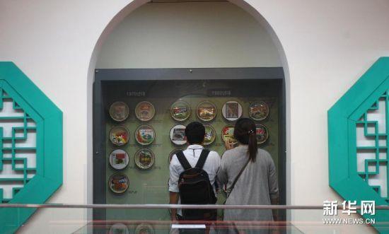 6月28日,在韩国仁川,两名参观者在炸酱面博物馆观看炸酱面的变迁史。