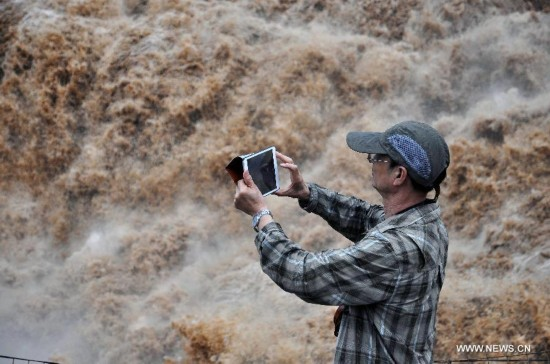 A tourist takes photos of the Hukou Waterfall of the Yellow River, north China's Shanxi Province, July 9, 2014. (Xinhua/Fan Minda)