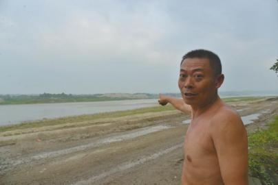 """村民手指正前江中,即""""陈国林乌木案""""发现处。"""