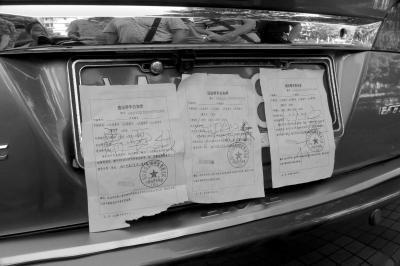 海口一轿车号牌上贴3罚单 车内放公务车通行证