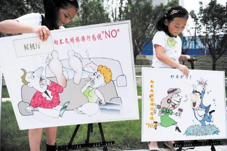图为小学生用卡通画宣传文明旅游