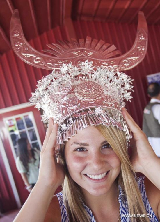 A woman tries to wear a silver head ornament during the 'Colorful Guizhou Exhibition' in the Town of Niagara-on-the-Lake, Ontario, Canada, July 22, 2014.