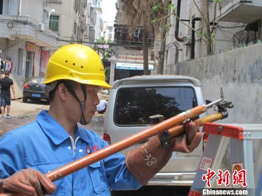 图为广东省中山市供电局抢修工人在海口市玉河维修更换供电设备。 付美斌 摄