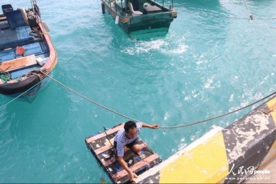 韦昌薪从码头登上渔船中