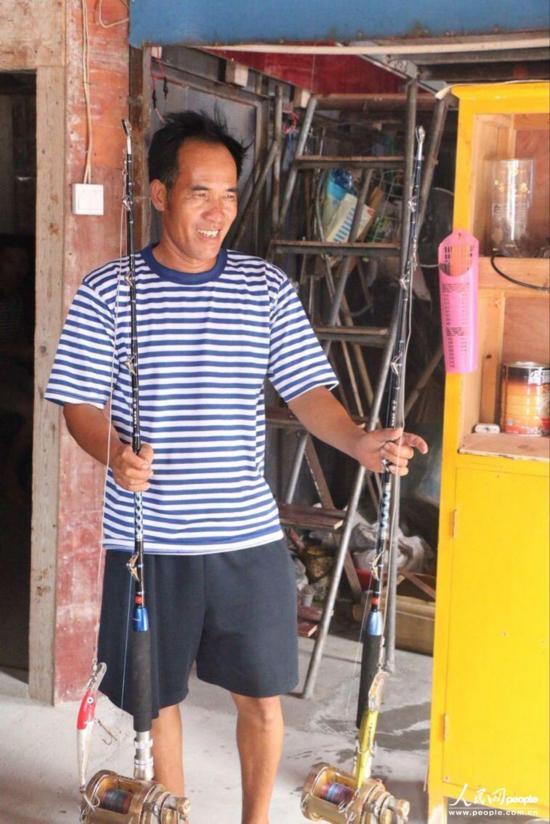韦昌薪向记者展示他捕鱼的工具。捕鱼的时候会根据鱼的种类不同多种工具并用