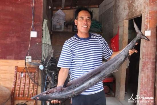 第九张 韦昌薪向记者展示前些天捕到的海鱼