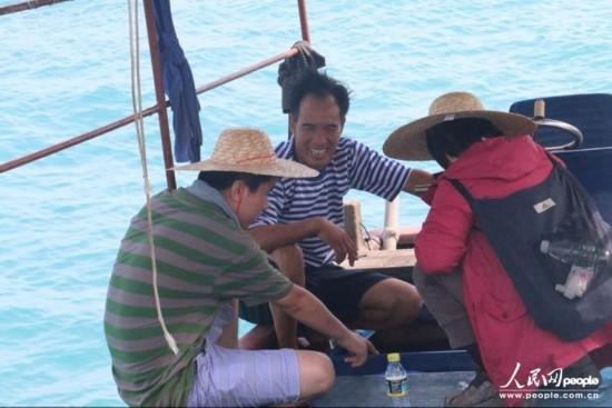 记者和韦昌薪在渔船上交谈