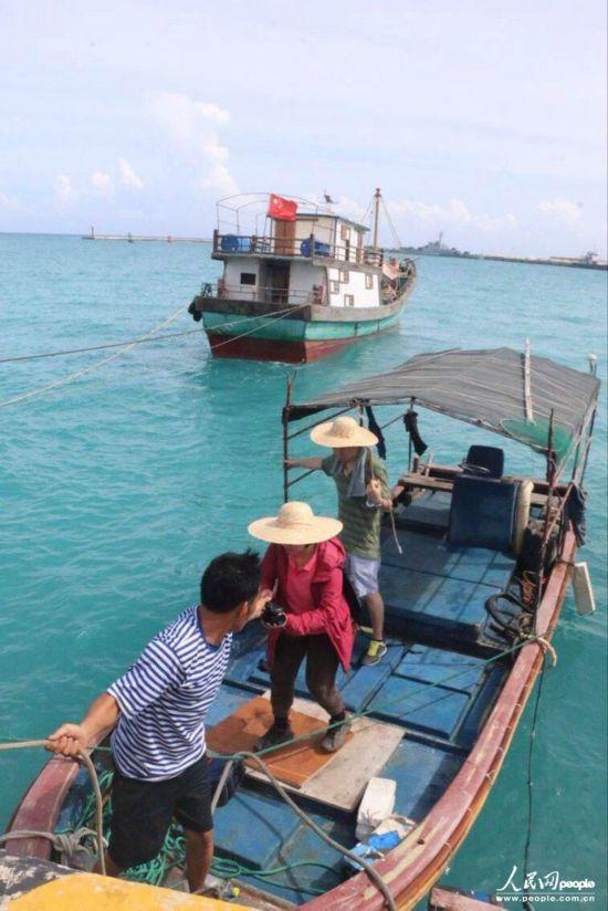 记者跟随韦昌薪从码头登上渔船中
