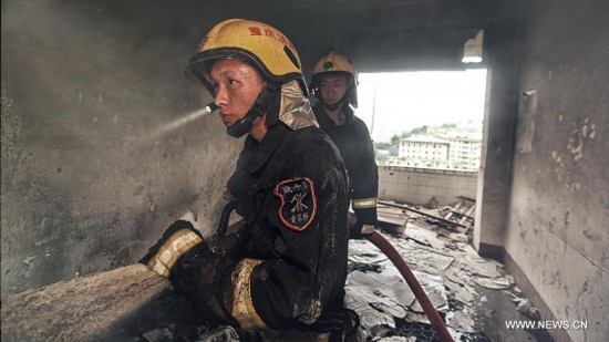 Firefighter Chen Jihang (front), a firefighter serving in Tongjiaqiao Fire Squadron, takes part in his first mission in Chongqing, southwest China, Aug. 23, 2013.