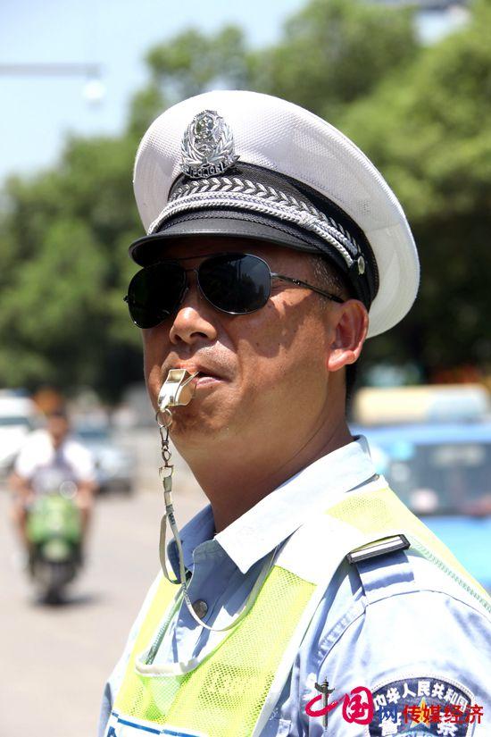 交警支队_7月30日,湖南省娄底交警支队中队长罗国平在坚守路面指挥交通