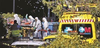 当地时间8月7日,西班牙马德里,多名医护人员身着防护服,抬着感染埃博拉病毒的西班牙天主教神父Miguel Pajares进入卡洛斯三世医院图片/IC