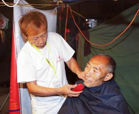 谢志刚在安置点为群众免费理发。(人民网 李发兴 摄)