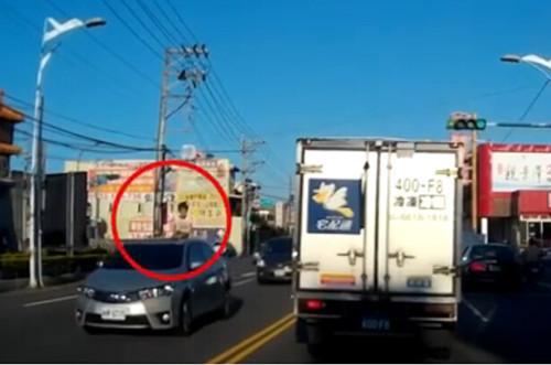 夫妇将孩子置於汽车顶部,在一条繁华的街道上行驶.路人看到此景象图片
