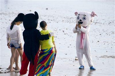 游客三亚湾与玩偶合影 玩偶索要照相费