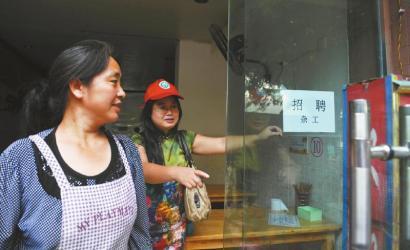 8月14日,市民志愿者体验城管执法招呼商家不要乱张贴。