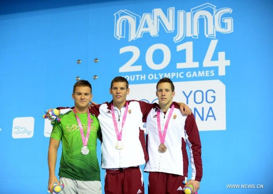 Gold medalist Benjamin Gratz (C) of Hungary, silver medalist Povilas Strazdas (L) of Lithuania and bronze medalist Norbert Szabo of Hungary pose on the podium after the men's 200m individual medley swimming event of Nanjing 2014 Youth Olympic Games