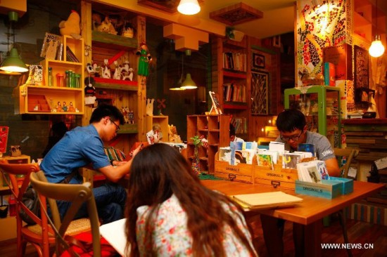 People read books at a bookstore at the Chilanqiao cultural block on Shuguangbei Street in Heifei, capital of east China's Anhui Province, Aug. 27, 2014. The cultural block, used to be a hub for junk dealers, has become a favorite destination for artists and culture lovers with its bookstores, galleries, bars and coffee houses and hostels after its reconstruction starting in 2012. (Xinhua/Zhu Weixi)