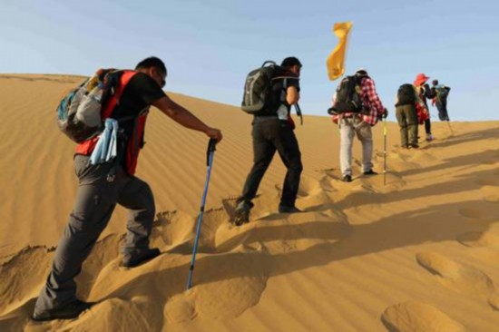 """""""善行天下""""隊員在沙漠中徒步行走.圖片"""