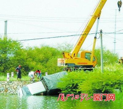 吊车正在把小货车吊出水面.