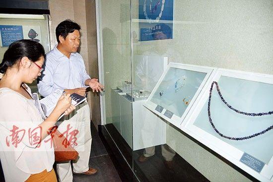 合浦汉代文化博物馆馆长廉世明在介绍馆藏的绿柱石饰品。