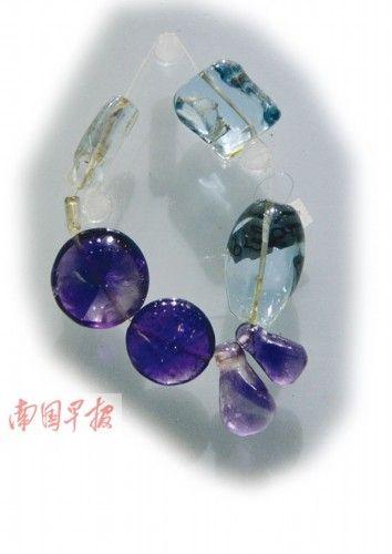 这串珠饰中的两颗浅蓝色晶体,被重新认定为海蓝宝石。