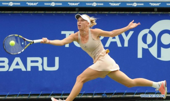 Caroline Wozniacki of Denmark hits a return against Carla Suarez Navarro of Spain during the third round match at the Toray Pan Pacific Open tournament in Tokyo, Japan, Sept. 19, 2014.