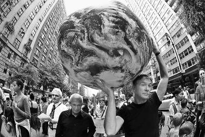 9月21日,在美国纽约,一名男子带着地球模型参加游行,呼吁关注气候变化问题。新华社/路透