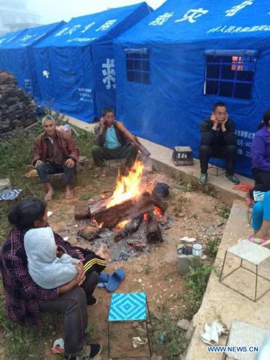 Photo taken with a mobile phone shows the villagers staying outside the tents in Mangfei Village of Yongping Township at Jinggu County of Pu'er City, southwest China's Yunnan Province, Oct. 8, 2014.