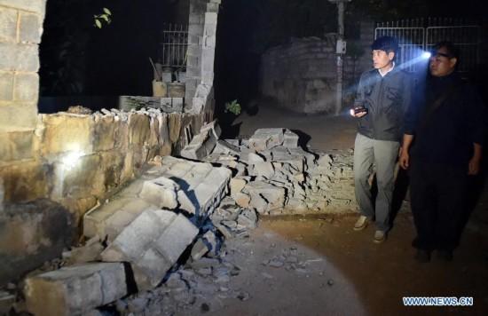 Villagers check the damaged house at Mangla Village of Yongping Township at Jinggu County of Pu'er City, southwest China's Yunnan Province, Oct. 8, 2014.