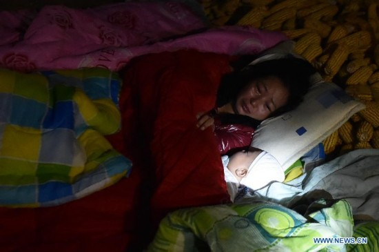 Villager Dao Yanling sleeps with her three-month-old son in the open air at Mangla Village of Yongping Township at Jinggu County of Pu'er City, southwest China's Yunnan Province, Oct. 8, 2014.