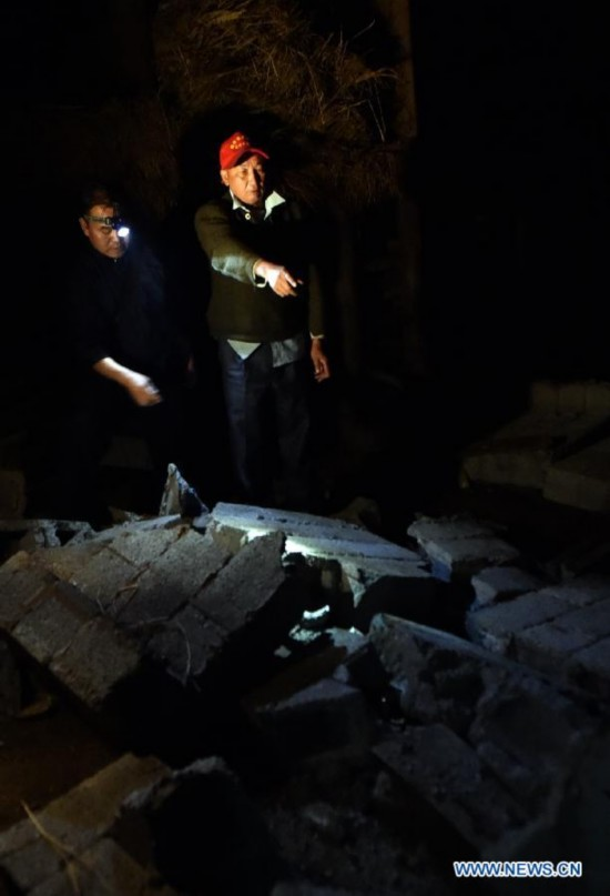 Villager Dao Wenguang (R) looks for his missing family members at Mangla Village of Yongping Township at Jinggu County of Pu'er City, southwest China's Yunnan Province, Oct. 8, 2014.